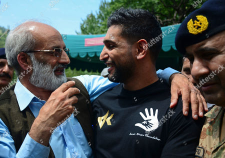 British boxer, promoter and philanthropist Amir Khan, center, meets Pakistani Kashmiris living at the Line of Control between Pakistan and Indian Kashmir, at the border area of Chakoti, in Pakistani Kashmir, . Khan visited the Line of Control on Tuesday to meet the families affected by India's ceasefire violations and to express solidarity with the people in Indian Kashmir