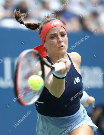 Nicole Gibbs, of the United States, returns a shot to Simona Halep, of Romania, during the first round of the US Open tennis tournament, in New York
