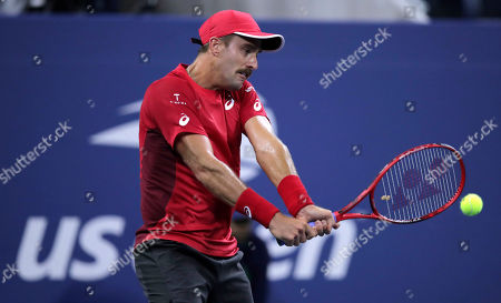 Steve Johnson, of the United States, returns to Nick Kyrgios, of Australia, during the first round of the U.S. Open tennis tournament in New York