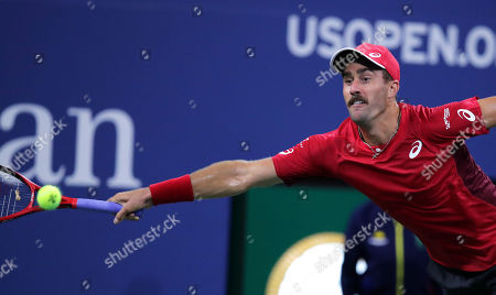 Steve Johnson reaches for a shot from Nick Kyrgios, of Australia, during the first round of the U.S. Open tennis tournament in New York
