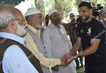 Amir Khan, British Boxer of Pakistani origin talks with people whose family members were killed by cross border firing by the Indian Army as he visits Chakothi, the capital of Pakistani administered Kashmir, near Line of Control (LoC) the de facto border between Pakistani and Indian administered Kashmir, Pakistan, 27 August 2019. Amir Khan said he visited Pakistani administered Kashmir to call for peace after the Indian government's decision to revoke the special status of Jammu and Kashmir and divide the state into federally administered territories, Jammu and Kashmir, and Ladakh. Rising tensions are renewed in the region as the Indian government on 05 August moved a resolution in the parliament that removes the special constitutional status granted to the disputed Kashmir region, a decision condemned by Pakistan. Kashmir has been a matter of dispute between India and Pakistan since 1947 when both countries became sovereign states.