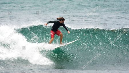 A surfer takes advantage of the waves after the passing of Tropical Storm Dorian, in eastern Barbados, . Tropical Storm Dorian caused power outages and downed trees in Barbados and St. Lucia. A still-uncertain long-term track showed the storm near Florida over the weekend