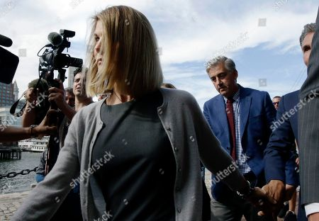 Lori Loughlin departs federal court, in Boston, after a hearing in a nationwide college admissions bribery scandal. At far right is her husband, clothing designer Mossimo Giannulli