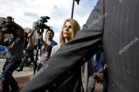 Lori Loughlin departs federal court, in Boston, holding hands with her husband, clothing designer Mossimo Giannulli, hidden at right, after a hearing in a nationwide college admissions bribery scandal