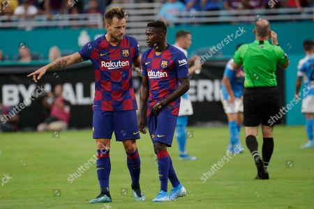 Barcelona midfielder Ivan Rakitic, left, talks with Moussa Wague, right, during the first half of a LaLiga-Serie A Cup soccer match against Napoli, in Miami Gardens, Fla