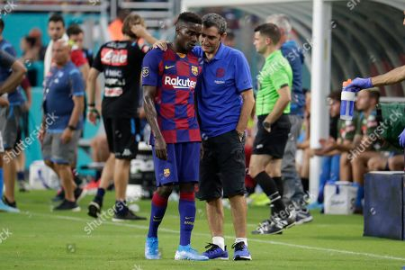 Barcelona head coach Ernesto Valverde, right, talks with Moussa Wague, left, during the first half of a LaLiga-Serie A Cup soccer match against Napoli, in Miami Gardens, Fla