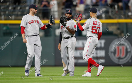 Boston Red Sox left fielder J.D. Martinez, center fielder Jackie Bradley Jr. and right fielder Mookie Betts, from left, celebrate the team's 10-6 win over the Colorado Rockies in a baseball game, in Denver