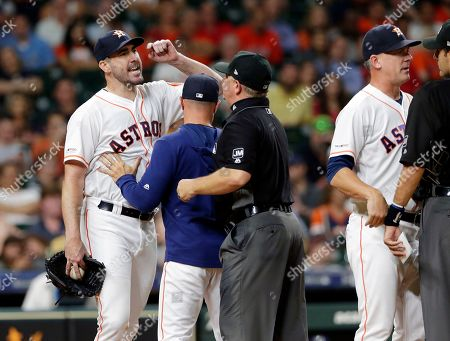 Houston Astros starting pitcher Justin Verlander, left, yells at home plate umpire Pat Hoberg, right, as Joe Espada, first base umpire Greg Gibson and manger A.J. Hinch get between them after Verlander was ejected by Hoberg during the sixth inning of a baseball game against the Tampa Bay Rays, in Houston