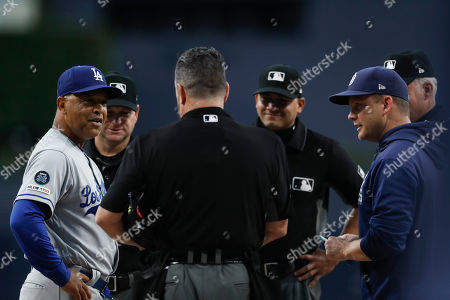 Los Angeles Dodgers manager Dave Roberts, left, and San Diego Padres manager Andy Green, right, meet with the umpires before a baseball game, in San Diego
