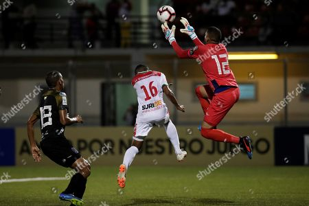 Stock Photo of Isiah Helstone (C) of SV Robinhood in action against Jose Guerra (R) and Angel Sanchez (L) of C.A. Independiente during a CONCACAF league soccer match between C.A Independiente of Panama and SV Robinhood of Suriname at the Agustin Muquita Sanchez Stadium in La Chorrera, Panama, 27 August 2019.