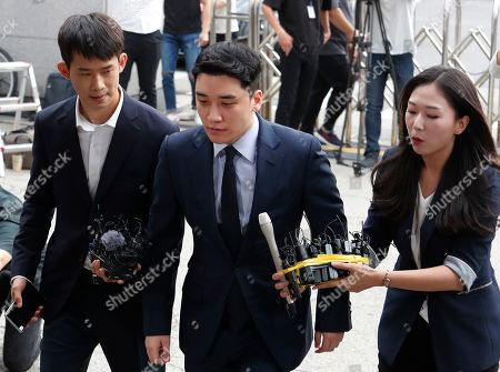 Lee Seung-hyun, center, a former member of the popular K-pop boy band Big Bang, arrives at the Seoul Metropolitan Police Agency's Intelligence Criminal Investigation Squad in Seoul, South Korea,. Police on Wednesday summoned Lee Seung-hyun on charges of gambling in a foreign country and securing gambling money in violation of the country's Foreign Exchange Transaction Act, Yonhap news agency reported
