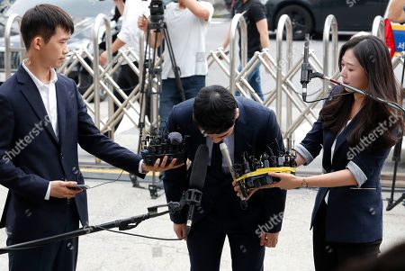 Lee Seung-hyun, center, a former member of the popular K-pop boy band Big Bang, bows upon his arrival at the Seoul Metropolitan Police Agency's Intelligence Criminal Investigation Squad in Seoul, South Korea,. Police on Wednesday summoned Lee Seung-hyun on charges of gambling in a foreign country and securing gambling money in violation of the country's Foreign Exchange Transaction Act, Yonhap news agency reported