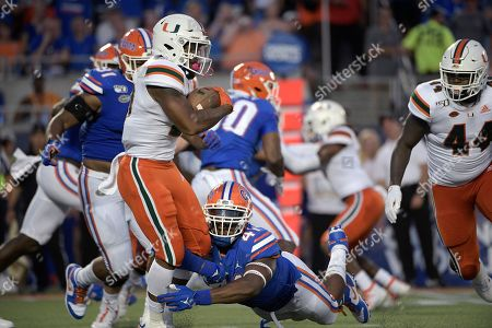 Miami running back Cam'Ron Harris (23) is tackled by Florida linebacker James Houston IV (41) after rushing for yardage during the first half of an NCAA college football game, in Orlando, Fla