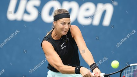 Mandy Minella, of Luxembourg, returns a shot to Belinda Bencic, of Switzerland, during the first round of the US Open tennis tournament, in New York