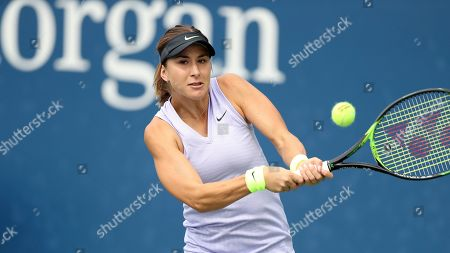 Belinda Bencic, of Switzerland, returns a shot to Mandy Minella, of Luxembourg, during the first round of the US Open tennis tournament, in New York
