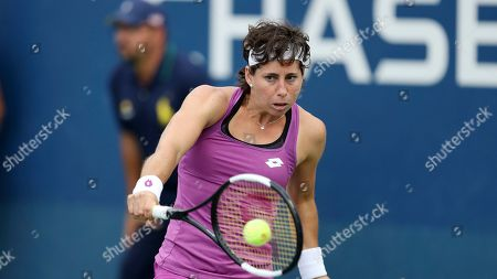 Carla Suarez Navarro, of Spain, returns a shot to Timea Babos, of Hungary, during the first round of the US Open tennis tournament, in New York
