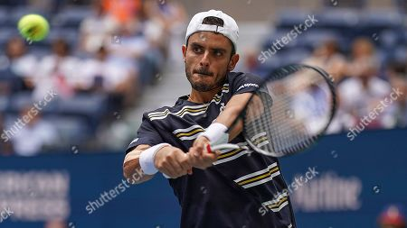 Thomas Fabbiano, of Italy, returns a shot to Dominic Thiem, of Austria, during the first round of the US Open tennis tournament, in New York