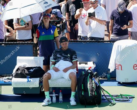 Stock Image of Lucas Pouille of France reacts on his chair as he rests between games alongside his smashed racket after losing the first two sets