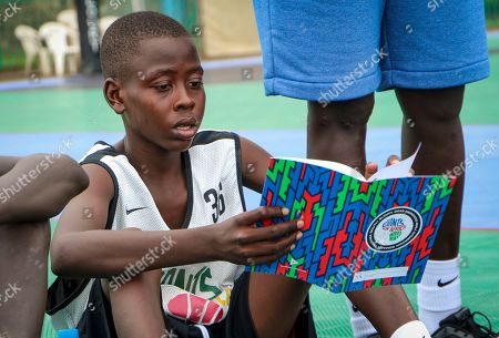 A participant in the Giants of Africa basketball camp reads his career goals from a notebook while sitting on a basketball court in Juba, South Sudan. Masai Ujiri, president of the Toronto Raptors basketball team who won the NBA championship for the first time this year, is founder of the Giants of Africa non-profit organization which runs a three-day training camp in South Sudan to empower youth through basketball