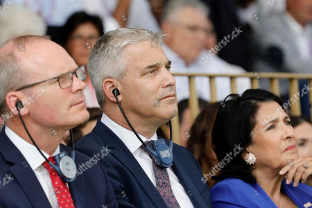 Britain's Brexit Minister for Exiting the European Union Stephen Barclay, center, and Ireland's Minister of Foreign Affairs Simon Coveney, left, listen to a speech at a business meeting in Paris, Wednesday, Aug.28, 2019