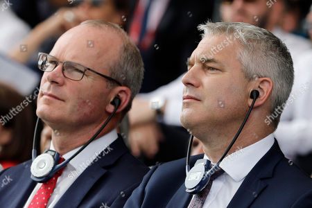 Britain's Brexit Minister for Exiting the European Union Stephen Barclay, right, and Ireland's Minister of Foreign Affairs Simon Coveney, left, listen to a speech at a business meeting in Paris, Wednesday, Aug.28, 2019