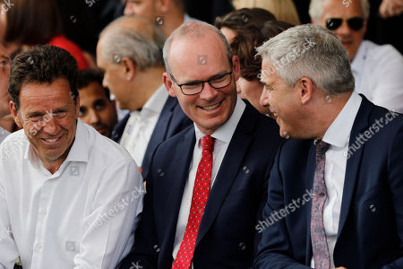 Britain's Brexit Minister for Exiting the European Union Stephen Barclay, right, and Ireland's Minister of Foreign Affairs Simon Coveney, center, chat while Head of the French businessmen organization (MEDEF) Geoffroy Roux de Bezieux, left, smiles during a business meeting in Paris, Wednesday, Aug.28, 2019