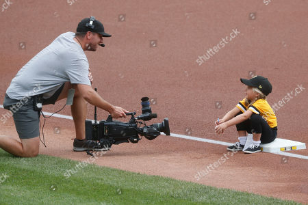 A stadium camera man takes video of the girl on third base that are part of the team's Sunday kids day feature before the start of a baseball game between the Pittsburgh Pirates and the Cincinnati Reds, in Pittsburgh