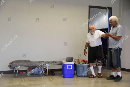 Victor Ortiz Martinez, 79, left, is guided by Hector Guzman at the William Rivera Vocational School converted into a temporary shelter, before the arrival of Tropical Storm Dorian, in Canovanas, Puerto Rico, . Dorian became a Category 1 hurricane on Wednesday as it struck the U.S. Virgin Islands, with forecasters saying it could grow to Category 3 status as it nears the U.S. mainland as early as the weekend