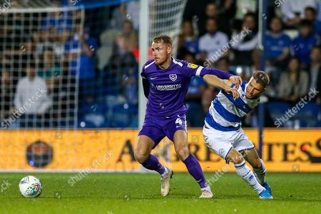 Portsmouth midfielder Tom Naylor (4) holds off Queens Park Rangers forward Jan Mlakar (16) during the EFL Cup match between Queens Park Rangers and Portsmouth at the Kiyan Prince Foundation Stadium, London