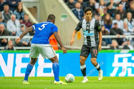 Yoshinori Muto (#13) of Newcastle United FC looks to take on Wes Morgan (#5) of Leicester City during the EFL Cup match between Newcastle United and Leicester City at St. James's Park, Newcastle