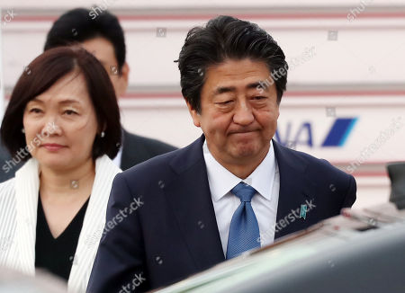 Shinzo Abe, accompanied by his wife Akie Abe, arrives at the Tokyo International Airport.