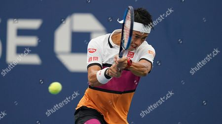 Stock Photo of Kei Nishikori, of Japan, returns a shot to Bradley Klahn, of the United States, during the second round of the US Open tennis tournament, in New York