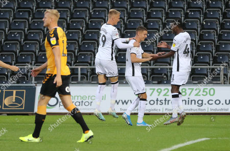 Kristoffer Peterson of Swansea City, centre, celebrates with Sam Surridge of Swansea City and Jordan Garrick of Swansea City after scoring goal in the opening minute of the match