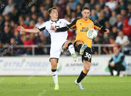 Tom Carroll of Swansea City and Jack Roles of Cambridge United compete for the ball