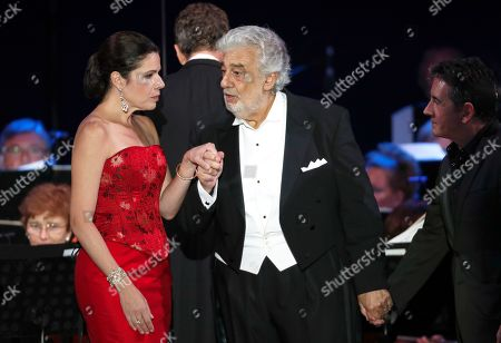 Stock Photo of Opera star Placido Domingo holds the hands of Ana Maria Martinez and Placido Domingo Jr., right, at the end of a concert in Szeged, Hungary, . Domingo continued his calendar of European engagements unabated despite allegations of sexual harassment, appearing Wednesday at a concert in southern Hungary to inaugurate a sports complex for a local Catholic diocese