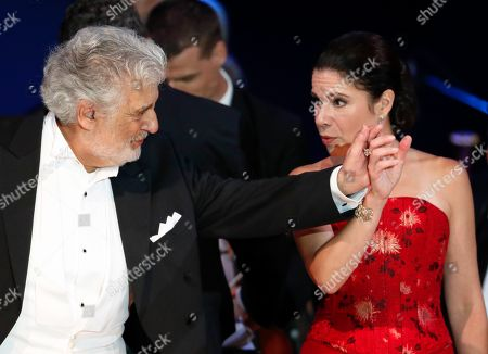 Opera star Placido Domingo holds the hand of Ana Maria Martinez at the end of a concert in Szeged, Hungary, . Domingo continued his calendar of European engagements unabated despite allegations of sexual harassment, appearing Wednesday at a concert in southern Hungary to inaugurate a sports complex for a local Catholic diocese