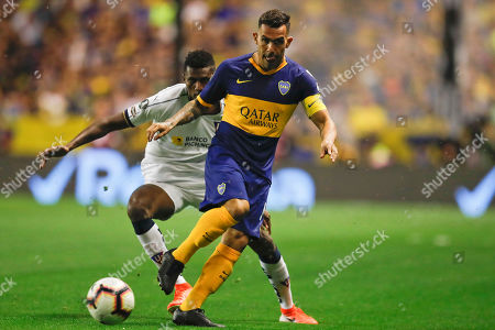 Carlos Tevez of Argentina's Boca Juniors, front, is challenged by Jose Ayovi of Ecuador's Liga Deportiva Universitaria during a quarter final second leg Copa Libertadores soccer match in Buenos Aires, Argentina