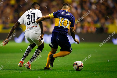 Carlos Tevez of Argentina's Boca Juniors, right, and Jose Ayovi of Ecuador's Liga Deportiva Universitaria compete for the ball during a quarter final second leg Copa Libertadores soccer match in Buenos Aires, Argentina