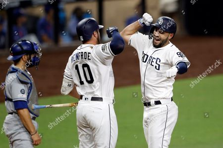 Stock Image of San Diego Padres' Eric Hosmer, right, celebrates with Hunter Renfroe (10) after hitting a home run as Los Angeles Dodgers catcher Russell Martin looks on at left, during the eighth inning of a baseball game, in San Diego