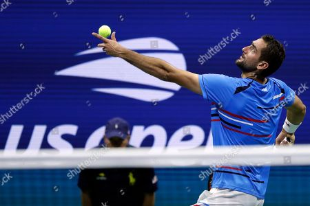 Marin Cilic, of Croatia, tosses the ball for a serve to Cedrik-Marcel Stebe, of Germany, during the second round of the U.S. Open tennis tournament, in New York