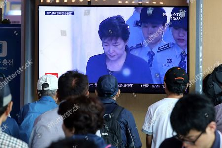 People watch a TV screen showing former South Korean President Park Geun-hye during a news program at the Seoul Railway Station in Seoul, South Korea, . South Korea's top court on Thursday sent back Park's corruption case to a lower court for separate trials for her previously convicted charges, a ruling that could increase her already-lengthy prison term
