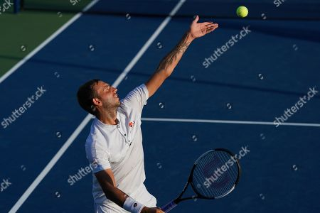 Dan Evans of Great Britain serves during pay in the Men's Doubles