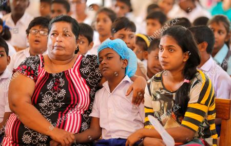 Survivors of the Easter Sunday attacks listen to Archbishop of Canterbury Justin Welby at St. Sebastian's church in Katuwapitiya village, Negombo, Sri Lanka, . More than 250 people were killed in coordinated suicide bomb attacks at three churches and three tourist hotels on Easter Sunday that were claimed by the Islamic State group and carried out by a local radicalized Muslim group