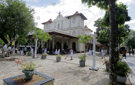 People clean the courtyard of the St. Sebastian's church, one of the sites of the Easter Sunday attacks, as they wait to welcome the Archbishop of Canterbury Justin Welby in Katuwapitiya village, Negombo, Sri Lanka, . More than 250 people were killed in coordinated suicide bomb attacks at three churches and three tourist hotels on Easter Sunday that were claimed by the Islamic State group and carried out by a local radicalized Muslim group