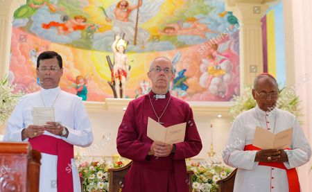 The Archbishop of Canterbury Justin Welby, center, pays homage to victims of the Easter Sunday attacks at St. Sebastian's church in Katuwapitiya village, Negombo, Sri Lanka, . More than 250 people were killed in coordinated suicide bomb attacks at three churches and three tourist hotels on Easter Sunday that were claimed by the Islamic State group and carried out by a local radicalized Muslim group