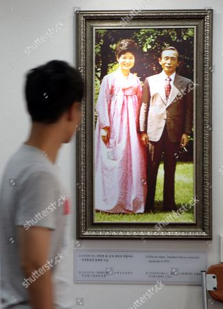 Stock Photo of A visitor looks at a photo of late President Park Chung-hee and his daughter and former President Park Geun-hye at the elder Park's birthplace in the southeastern city of Gumi, South Korea, 29August 2019. In its verdict hearing over a corruption case that involves Park, her friend Choi Soon-sil and Samsung Group heir Lee Jae-yong, the Supreme Court sent the case to the Seoul High Court, nullifying the lower court's rulings that sentenced Park, Lee and Choi to 25 years in prison, a two-and-half year suspended prison term and 20 years in prison, respectively.