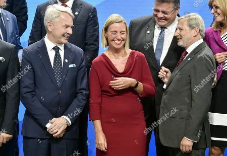 Finnish Foreign Minister Pekka Haavisto, European Union Foreign Policy Chief Federica Mogherini and European Commissioner for European Neighbourhood Policy and Enlargement Negotiations Johannes Hahn share a laugh during a group photo session at the Informal Meeting of EU Foreign Ministers