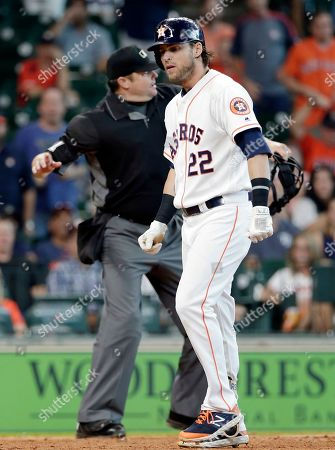Home plate umpire Jordan Baker (71) winds up to eject Houston Astros' Josh Reddick (22) after Reddick argued a strike call during the ninth inning of a baseball game against the Tampa Bay Rays, in Houston