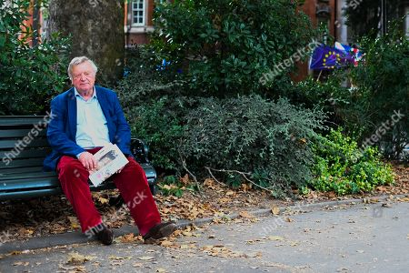 Politician Ken Clarke sits on a bench in Victoria Tower Gardens with European flags in the background.