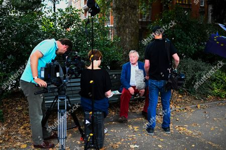 Politician Ken Clarke gives an interview to a film crew in Victoria Tower Gardens near the Houses of Parliament.